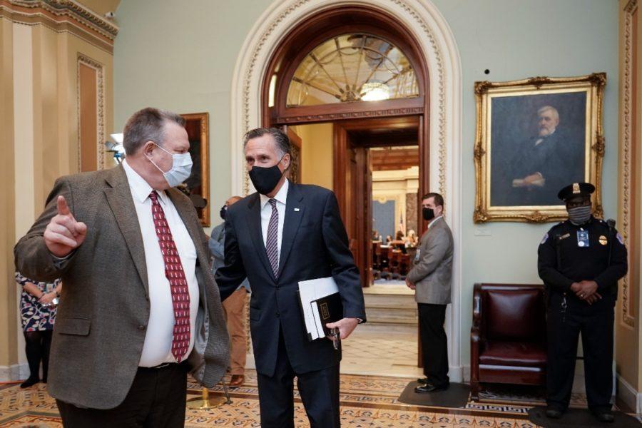 Sen. Jon Tester and Sen. Mitt Romney leave the Senate chamber on Friday, Feb. 12, 2021.